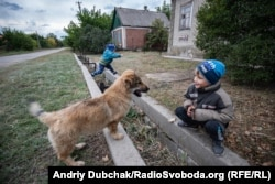 Vova, 7, and his little brother Stepan play with a dog in Luhanske.