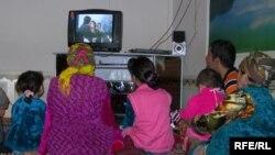 Өзбекстандагы бир үй-бүлө телевизор көрүп отурат.
