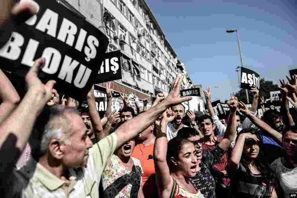 """Турецкая полиция в пятницу утром начала широкомасштабную антитеррористическую операцию по всей стране, чтобы выявить возможных сторонников""""Исламского Государства""""и экстремистскойКурдской рабочей партии На фото - люди с плакатами """"мир"""" во время демонстрации 26 июля"""
