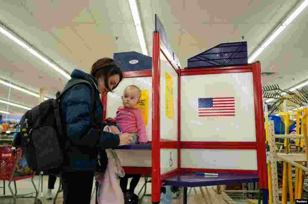 ریچل بنت، از آیووا، همراه دخترش املیا، رای خود را به صندوق میاندازد.دو حزب اصلی آمریکا، یعنی حزب جمهوریخواه و حزب دمکرات، و نیز نامزدها و چهرههای شناختهشده این دو حزب، در چند هفته اخیر کارزار انتخاباتی داغی را در گوشه و کنار آمریکا برگزار کردهاند.