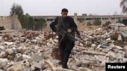 Сирия ерікті армиясының жауынгері қираған ғимарат орнында жүр. Алеппо, 17 желтоқсан 2012 жыл. (Көрнекі сурет).