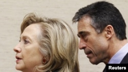 U.S. Secretary of State Hillary Clinton (left) and NATO Secretary-General Anders Fogh Rasmussen arrive at a NATO defense and foreign ministers' meeting at alliance headquarters in Brussels.