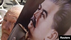 Иосиф Сталиннің суретін көтеріп тұрған Екінші дүниежүзілік соғыс ардагері. Украина, Запорожье қаласы, 5 мамыр 2010 жыл (Көрнекі сурет).