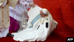 Папе римскому Франциску помогают подняться после падения