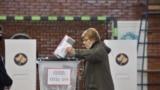 Një grua duke votuar në një qendër votimi në Prishtinë për zgjedhjet parlamentare të 14 shkurtit.