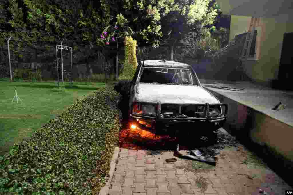 A burned-out vehicle smolders inside the U.S. Consulate compound.