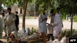 Victims are treated outside a hospital following a suicide bomb attack targeting a police station in Lakki Marwat.