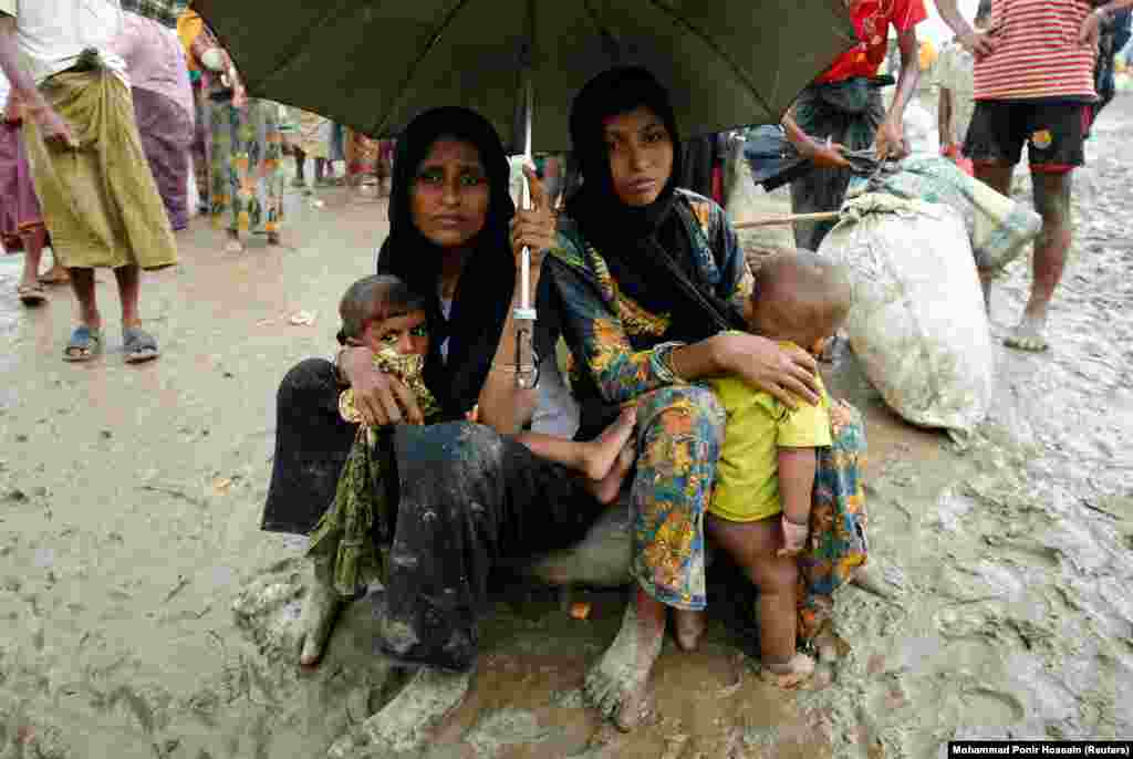 Rohingya refugees sit with their belongings during heavy rain after they were detained by border guards for illegally crossing into Bangladesh.