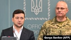Ukrainian President Volodymyr Zelensky speaks, flanked by Ruslan Khomchak, military commander of the Armed Forces of Ukraine, at a briefing following an outbreak of violence with Russia-backed separatists, in Kyiv on February 18.