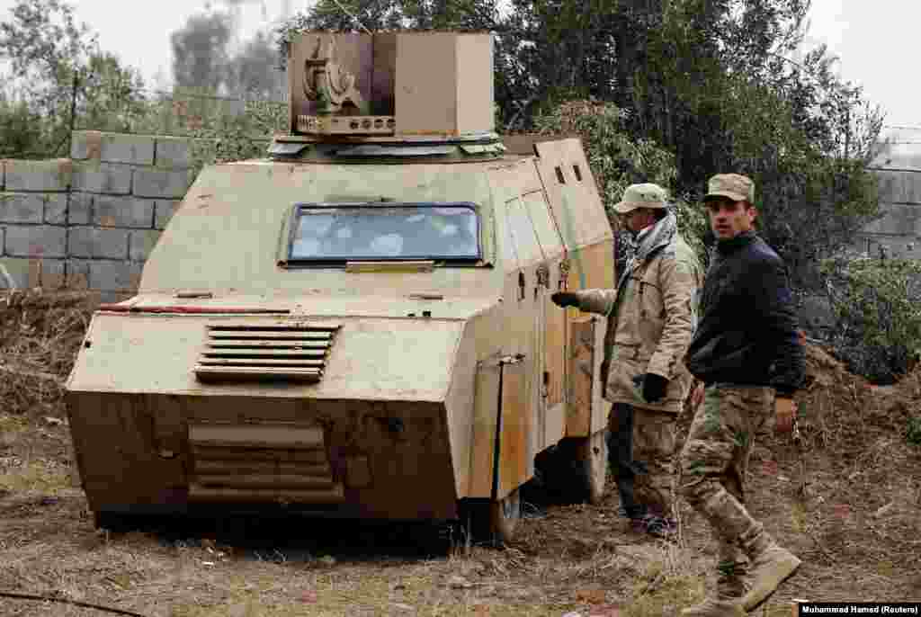 Iraqi soldiers inspect a captured vehicle designed for a suicide car bombing in Mosul, in northern Iraq. Crudely armored vehicles like this are packed with explosives and can be extremely difficult to stop when driven straight at coalition battle positions.