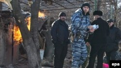 Soldiers and police work at a house destroyed during a special operation in Grozny. Critics say Moscow's military approach to the region's problems is self-defeating.