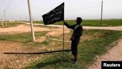 أحد مقاتلي جبهة النصرة في سوريا يمسك بعلم في محافظة الرقة.