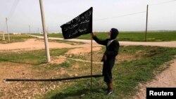 Боец «Ан-Нусры» с флагом исламистов. Север Сирии, провинция Ракка, март 2013 г.