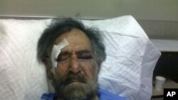 Syrian cartoonist Ali Ferzat lies injured at a hospital in Damascus