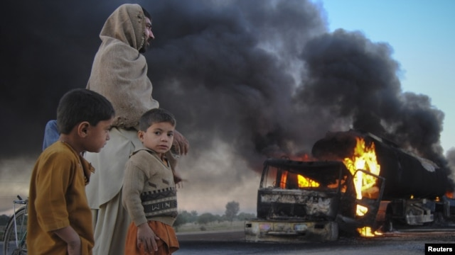 Pakistanis watch fuel trucks that were set ablaze in the Bolan district of Baluchistan Province on December 12.