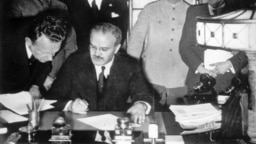 Soviet Foreign Minister Vyacheslav Molotov (seated) signs the German-Soviet non-aggression pact in Moscow on August 23.