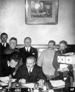 Veaceslav Molotov, așezat, semnează Pactul de neagresiune germano-sovietic la Moscova, 23 august 1939