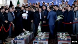 Iranian President Hassan Rohani (left) prays near the coffins of victims who died in a terror attack at the Iranian parliament in Tehran.