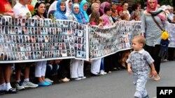 1995 жылғы Сребреница қырғынында өлгендердің жаңадан табылған мәйітін күтіп тұрған демонстранттар. 9 шілде 2013 жыл