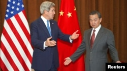 Chinese Foreign Minister Wang Yi (right) meets with U.S. Secretary of State John Kerry in Beijing on April 13.