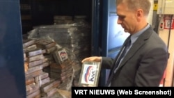 Представитель бельгийской полиции держит в руках брикет с кокаином, маркированный логотипом «Единой России». Кадр из видео бельгийской телерадиокомпании VRT.