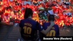 Njerëzit para një vendi përkujtues me lule dhe qirinj për nder të viktimave të sulmit terrorist në Barcelonë