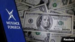 Смартфон с логотипом панамской офшорной компании Mossack Fonseca на фоне банкнот номиналом один доллар.