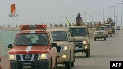 An image taken from Bahrain TV shows the vanguard of a contingent of Gulf troops arriving in Bahrain across a causeway from Saudi Arabia.
