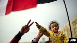 An Egyptian girl sits on the shoulders of her father during ongoing pro-reform demonstrations on Cairo's Tahrir Square.