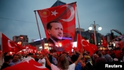 A supporter holds a flag depicting Turkish President Tayyip Erdogan during a pro-government demonstration in Ankara, Turkey on July 20.
