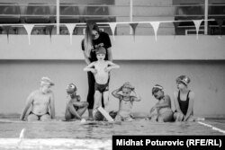 A trainer works with young swimmers in Sarajevo