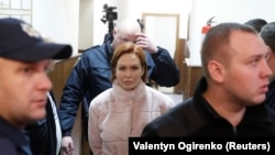 Yulia Kuzmenko is escorted to a court hearing in Kyiv on December 13.