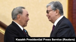 Kazakhstan - Acting President of Kazakhstan Kassym-Jomart Tokayev (R) shakes hands with his predecessor Nursultan Nazarbayev during a joint session of the houses of parliament in Astana, Kazakhstan March 20, 2019. Kazakh Presidential Press Service/Handout
