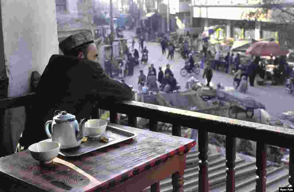 A man watches the market crowd from the second floor of a teahouse. - The densely packed houses and narrow lanes of old Kashgar are said to be the best-preserved examples of a traditional Islamic city in all of China. (All photos www.ryanpyle.com)