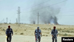 Iraqi police scan for land mines near the Rumaila oil field in Basrah province.
