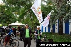 Волонтеры выдвигаются к месту старта. В руках у одного из них флаг Дня города и флаг Veloquest'а. Алматы, 13 сентября 2015 года.