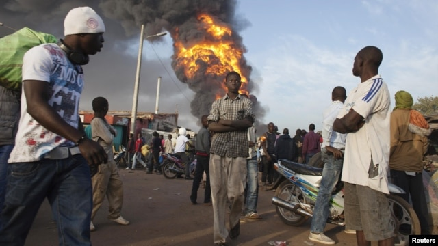 Onlookers walk past a fire at Ngolonina market in the Malian capital of Bamako on January 12.