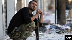 A Syrian rebel fighter watches the sky after hearing a helicopter Aleppo's al-Amiriya neighborhood on September 24.