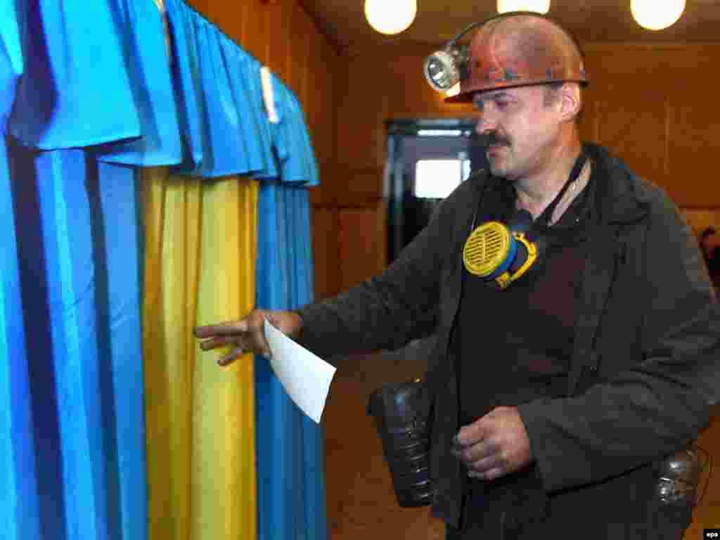 Шахтар заходить до кабінки для голосування в Донецьку