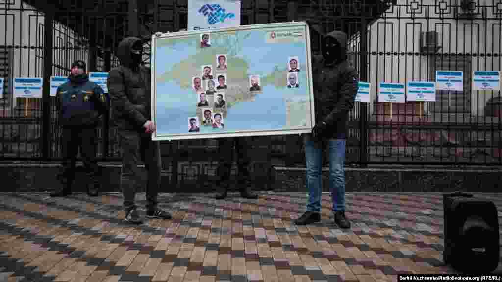 Переодягнені силовики в чорних масках тримали карту Криму з фотографіями зниклих людей