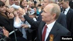 Президент России здоровается со встречающими его жителями Севастополя во время визита в аннексированный Москвой Крым. 9 мая 2014 года.