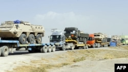 Pakistani drivers guide trailers carrying armored vehicles for NATO forces near Quetta. (file photo)