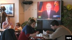 Russians listen to an address by then-President Vladimir Putin. Growing wealth in Russia has come at the expense of civil society and certain freedoms.