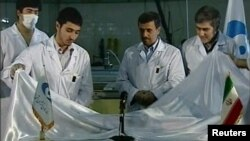 Iranian President Mahmud Ahmadinejad (center) looks on as scientists unveil a fuel rod at the Tehran Research Reactor.