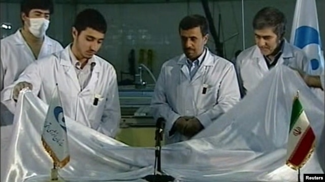 Iranian President Mahmud Ahmadinejad looks on next to scientists unveiling a fuel rod at the Tehran Research Reactor in February.