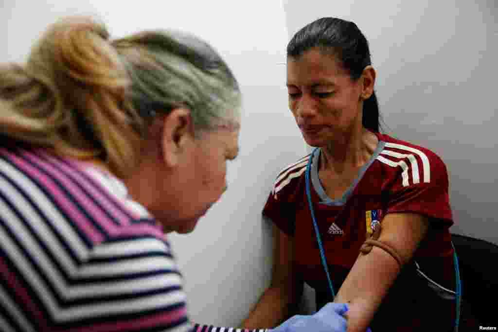 """""""Я не смогла найти ни [контрацептивных] инъекций, ни таблеток – ничего. На черном рынке это очень дорого, но сейчас препараты почти невозможно найти даже там"""", – рассказывает одна из женщин. На фото: врач берет кровь у Геральдины Рокки для теста на беременность"""