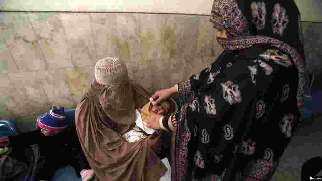 A polio worker gives polio vaccine drops to a child at Lady Reading hospital in Peshawar on December 19. (Reuters/Fayaz Aziz)