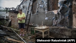 Женщина у своего разрушенного дома после обстрела между украинскими силами и сепаратистами, 60 км от Луганска