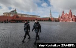 Police officers on a deserted Red Square in front of the Kremlin in Moscow on April 17