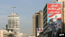 A poster of slain former Lebanese Prime Minister Rafik Hariri hangs from a building still bearing the scars of Lebanon's civil war in Beirut.